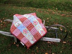 """Country Red"" Lap Quilt made from 100% recycled bed linens, aprons and clothes. Quilt batt also made form 100% recycled polyester. Size 30"" x 33""."