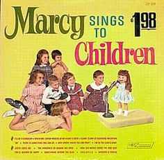 Marcy sings to children.  (The forerunner of American Idol.)