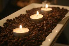 ¿Te gusta el aroma del café? Llena un bowl o un plato largo con granos de café y coloca encima velas pequeñas, como en la imagen. Al quemarlas, todo el espacio se impregnará con olor fresco a café. Tip de @Juliana Familia