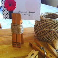 DIY rustic place card holders.  Dyed clothes pegs with coffee Put 2 dark lines with a marker to accent pegs Wrapped twine around and hot glued to hold :-)