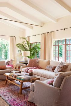 A pretty living room with California happy chic, linen furniture, and pops of pink.