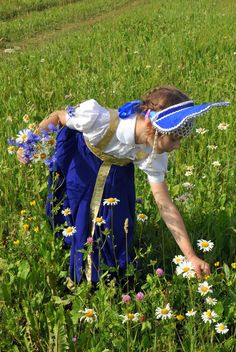 A little girl in the Russian traditional costume is picking wild flowers.