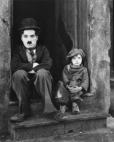 "Charlie Chaplin in ""The Kid"" 1921 silent dramedy film written, produced by, directed by, and starring Charlie Chaplin and Jackie Coogan as his adopted son and sidekick - Wikipedia"
