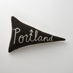 "This Portland pillow is adorable... too expensive for my budget, though.   ""Home Team Pennant Pillows"", $75.00, a Schoolhouse Electric exclusive:  These fun hometown-inspired pennant pillows will have fans cheering. Proudly crafted in Portland, OR, by a co. that produces authentic letterman jackets, each pillow is made of fine melton wool. Pillows feature chain-stitched lettering, cotton piping, cotton pebble cloth backing, and organic cotton fill (Dimensions: 22""L, 14""W)."