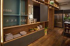 A parede lateral ocupa toda a extensão da parede e é multifuncional: serve para armazenar objetos, é a base da TV e da lareira e também pode se fazer de buffet em eventos.