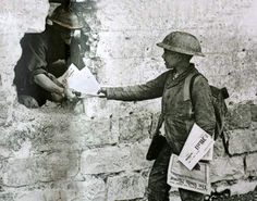 A newspaper seller hands copies of the Daily Mail and the Mirror to a British soldier in Arras