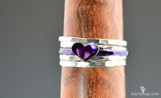 This #ring is #handmade from hammered sterling silver wire with a 5 by 7mm sterling silver heart. This ring has a shiny #violet purple nanoceramic coating over the silver to c... #alari #alaridesign #bff_ring #initial_heart_ring #initial_ring #jewelry #personalized_ring #purple_heart_ring #purple_ring #stacking_ring #sterling_silver #valentines_day #violet_ring #violet_silver