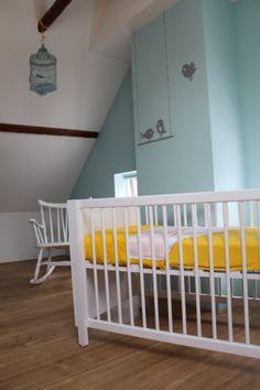 Babykamer, geel met blauw. Voor jongetjes en meisjes. Met vogeltjes op de muur geschilderd, vogelhuisjes aan de balken opgehangen, en open kastjes in de vorm van vogelhuisjes om boeken bijv. in te doen.