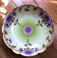 Beautiful porcelain Limoges bowl with purple flowers, circa 1904, Stamped on the bottom Limoges, France T& V and Hand Painted Stouffer Scalloped trim with gold accents. Early 20th Century French Hand painted porcelain.