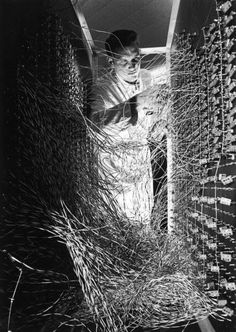 A male technician stands and adjusts the wiring at the rear of a large computer designed to monitor water depth and soil quality in Phoenix, Arizona, 1965