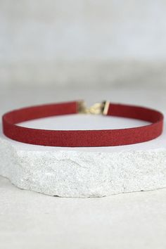 "We've got heart eyes for the Love Connection Wine Red Suede Choker! Soft vegan leather choker has gold ends that fasten behind the neck. Necklace measures 13"" around, plus a 2.5"" extender chain."
