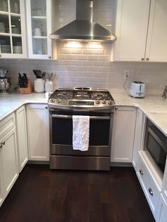 Subway tile backsplash, range hood, slide in gas range