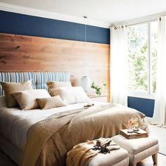 Dormitorio con pared azul, cabecero de madera y banquetas a los pies de la cama_00390674