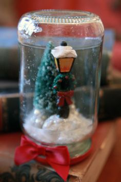 DIY waterless jar snowglobe. Bottle brush tree cake topper. I added beads and glitter to the fake snow (the shredded plastic kind to prevent excess moisture.)