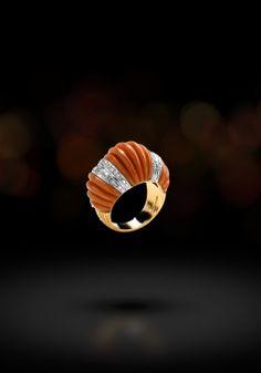Anello in oro giallo e bianco 18 kt montato con brillanti e corallo rosso inciso. (Ring in 18kts yellow and white gold with diamonds and engraved red coral.)  Sortija en oro blanco y amarillo de 18 kt con diamantes y coral rojo esculpido.