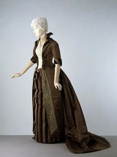 Dress, c.1888 Great Britain  This trained overdress is styled to suggest a man's coat of the Directoire period in France. The Queen magazine of Aug 1888 illustrated a very similar 'Directoire' reception dress, & in Nov of that year commented: 'the petticoat falls in gathers from the waist, corresponding with the large revers & the large cuffs. The sides of the coat hang down plain & straight, all the fullness being gathered into a cluster in the centre of the back below the waist.'  V Museum