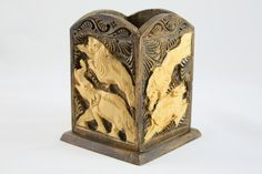 Wooden pen stand with hand carved images of animal prints.
