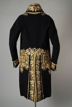 Back view, court coat, 1750-1800. Dark blue wool plain weave richly embroidered with floral motifs and leaves at center front, pocket and back in cream and yellow silk.
