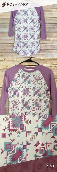 "LuLaRoe Purple Tribal Print Randy Tee NWOT At LuLaRoe, comfort is key and we often liken our dresses and skirts to a simple t-shirt in terms of their wearability and comfort. With LuLaRoe's Randy shirt, we have a t-shirt to offer. This unisex knit shirt resembles a baseball T with its raglan, mid-length sleeves in a contrasting, patterned fabric. It is everything a t-shirt should be: stylish, easy, and comfortable.  Length 28"". Excellent condition. No trades, please! Offers welcome. LuLaRoe…"
