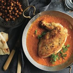 Golden roasted chicken over a rich, smooth sauce. Pair with oven-roasted chickpeas and cilantro. Get this chicken curry recipe and more at Chatelaine.com.