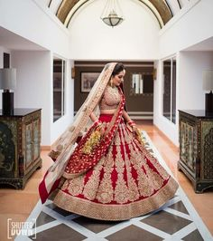 twirling indian bride in a full bridal lehenga and jewellery.
