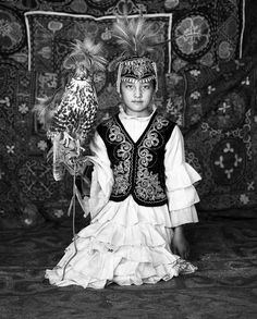 Kazakh girk in traditional dress with hawk. Kazakhstan, Central Asia.