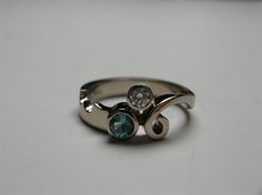 An white gold engagement ring, with a green tourmaline and diamond. The band has like a little bight taken out of it to make it more personal, on the other side there is a swirl a spiral coming to met the stones. Green Tourmaline, Spiral, Silver Rings, Stones, White Gold, Engagement Rings, Jewellery, Band, Diamond