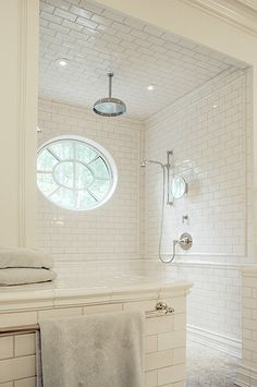 A large wonderful shower with lots of light... and lots of white tile...