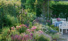 Ganz nah dran sind Sie mit einer gemütlichen Laube direkt neben einem blühenden Beet – so kann das ideale Gartenzimmer aussehen. Die Pergola bietet den schützenden Rahmen und schafft Geborgenheit. Ebenso wichtig ist es, nah an einem wirklich schönen Fleck im Garten zu sein, wie hier am Beet mit blühendem Lavendel, Steppen-Salbei, Rosen und Zierlauch