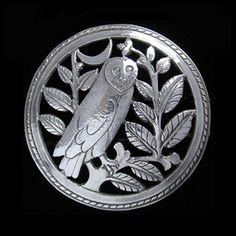 This is not contemporary - image from a gallery of vintage and/or antique objects. BERNARD CUZNER (1877-1956)  A silver domed Arts & Crafts, pierced and chased brooch of an owl perched amongst leaves before a crescent moon.