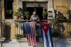 A man stands on his balcony, decorated with U.S. and Cuban flags, in Old Havana two days after the U.S. and Cuba announced the restoration of diplomatic ties. (Photo: Ramon Espinosa/AP)   This story i