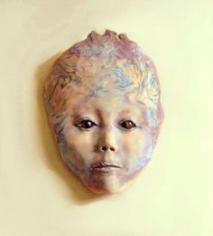 """This is the spirit of rocks and minerals. This child face represents nature and the earth.  A sweet little child face that is at once innocent and yet thoughtfully dignified.  The eyes in this sculpture are Tiger Eye gemstones that are deep and luminous in their nature.  Strata of different colors of rocks and minerals run throughout this sculpture.""  by Jane Priser"