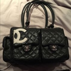 Chanel Cambon Reporter Bag Black quilted smooth lambskin leather, rare Chanel Cambon Reporter bag w/ silvertone hardware, 5 exterior pockets, white interlocking CC logo on the front, dual top shoulder straps, hot pink logo stamped interior lining, 2 interior wall pockets, 1 interior zip pocket & top zip closure. Will ship w/blk Chanel dust bag.  No visible scratches on hardware. Faint ware on interior lining, which can be cleaned & only slight scuffs on the back exterior.  Inside corner…