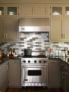 Scene Stealer. In a U-shape kitchen with little wall space, the range offers the only opportunity to make a statement with backsplash tile. Echoing the neutral hues of its surroundings, the recycled-aluminum tile acts as a dramatic accent.