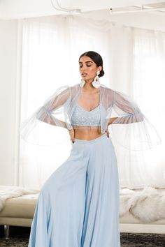 A powder blue, spaghetti strap top with raindrop beading is styled with a pair of delicate, wide-leg pants and a tulle, bell-sleeved bolero. Indian Fashion Trends, Indian Fashion Dresses, Indian Bridal Outfits, Indian Gowns Dresses, Dress Indian Style, Indian Designer Outfits, Fashion Outfits, Stylish Dress Designs, Stylish Dresses