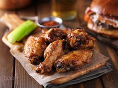 crispy barbecue chicken wings with celery on wooden serving tray - crispy barbecue chicken wings with celery on wooden serving tray