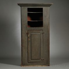 Blue/Green-painted Cupboard, New England, 18th century, with deep molded cornice above a molded case with two concave open shelves above a paneled cupboard door and molded base, (imperfections), ht. 79 1/2, cornice wd. 43 3/4, case wd. 36, case dp. 17 in.