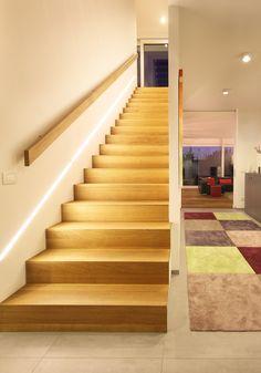 Modernes Treppendesign mit LED-Lichtband. Gerade Betontreppe mit Holzbelag und Handlauf im Hauseingang. Projekt by www.flow-architektur.de
