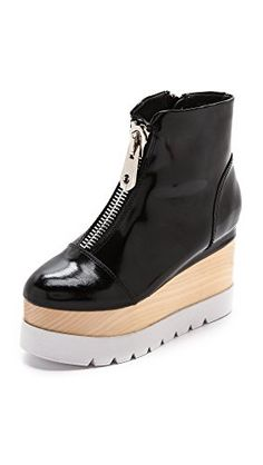 new product 7e42e d9bdc A wooden wedge and foam platform bring daring height to these patent leather  Jeffrey Campbell booties. A slim, tonal zip closes the side, and the hefty,  ...