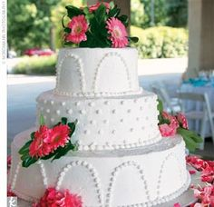 The buttercream iced, chocolate wedding cake was layered with raspberry filling and topped with pink gerbera daisies.
