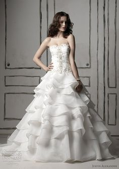 Layered organza ball gown with draped modified sweetheart neckline bodice accented with crystal beading.