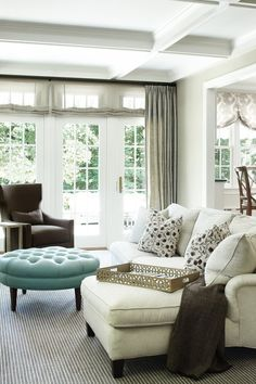Coffered ceiling, a mix of patterns, and statement blue ottoman offset a neutral color palette.