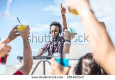 dj set at the beach party. dj spins the music and people is excited with hands up. concept about party, music and people - stock photo