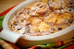 Bread and Butter Pudding - a British dessert flavored with candied lemon peel. Buttered, browned baguette slices are covered with a rich custard, topped with almonds & golden raisins, and baked in a gratin dish.