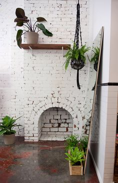 Simple painted brickwork is enlivened with hits of greenery. The high shelf brings a touch of the unexpected