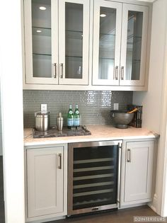 Fabulous butler's pantry features glass-front upper cabinets and tan lower cabinets fitted with a glass door wine cooler paired with gray and white marble countertops and a gray glass tiled backsplash.