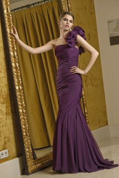 Mother of the Bride dress by VM Collection 70210. Glamorous one shoulder fitted mermaid gown. All over ruching and wire edged ruffles at the shoulder give it a couture look. Mid back with covered buttons. The Fabric in this style is Chiffon.
