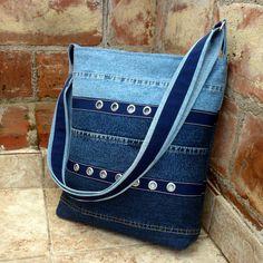 Džíska unisex s kroužky a štepováním Větší džínová kabelka je ušita z odstínů recy džínoviny od tmavo po světle modrou. Přední strana je zdobená aplikací modrého popruhu zdobeného štepováním a kovovými kroužky, na zadní straně je pouze štepování. Kabelka je důkladně podlepená, je pevná, dobře drží tvar, džínová podšívka je opatřena šesti kapsami. ...