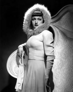"""""""Flattering blue fox makes a smart frame for the face of Dorothy Lamour. With an evening gown of white crepe, designed by Edith Head, Miss Lamour wears a zippered jacket with an attached hood trimmed in this luxurious fur."""""""