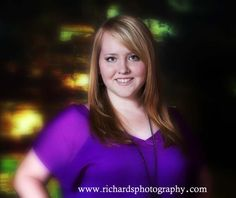 Indoor senior portrait of girl wearing purple with abstract background.